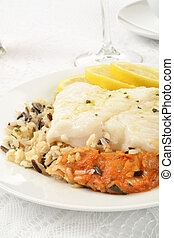 Cod Provencal on wild rice with slices of lemon