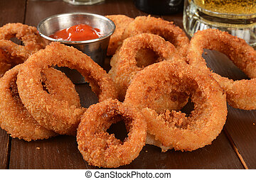 Onion rings - Crispy golden onion rings with a mug of beer