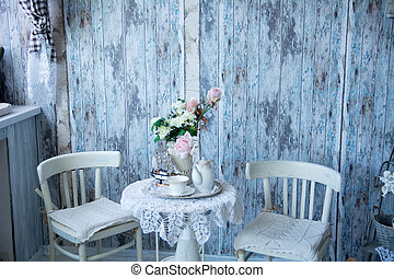 The interior in blue tones with two chairs and a vase with...
