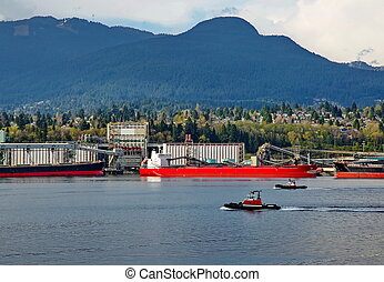 Sea port of North Vancouver - Two tugboats go along the port...