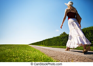 Young woman walking fast on a road. Wide angle view.