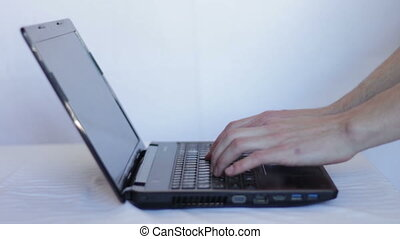 The man opens the the notebook and typing on laptop keyboard...