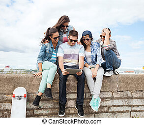 group of teenagers looking at tablet pc - summer holidays,...