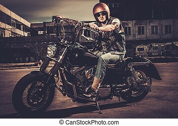 Tattooed biker and his bobber style motorcycle on a city...