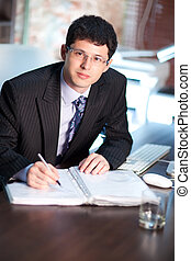 Young businessman signing a document
