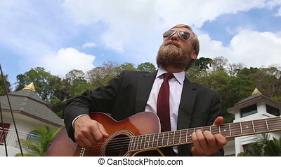 bearded man  plays guitar against villas and clouds above