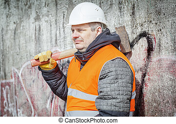 Worker with sledge hammer near the wall