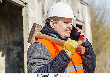 Worker with sledge hammer talking on cell phone