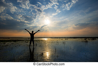 Man holding arms up in praise in sunset while being in water...