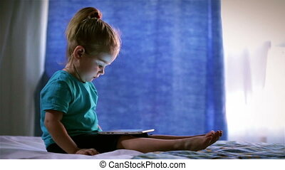 Cute baby girl use a Tablet PC, touches finger screen