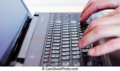 Man typing on laptop keyboard.