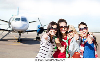 happy teenage girls showing thumbs up at airport - summer...
