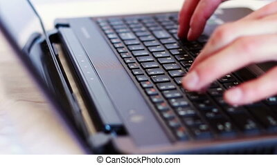 Man typing on laptop keyboard - Human hands typing on a...
