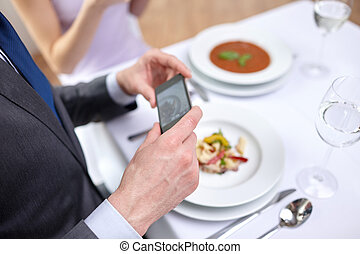 close up of couple with smartphones at restaurant - people,...