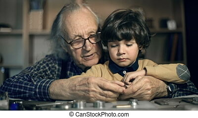 Acquiring Skills - Close up of senior man with grandson...