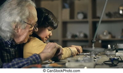 Little Watchmaker - Close up of little boy learning to mend...