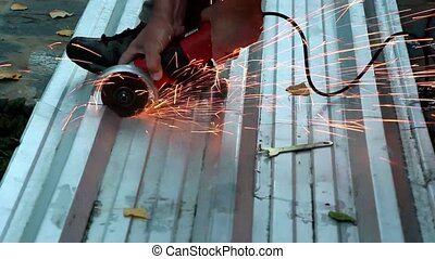 Angle grinder - A worker cuts a piece of metal into two...