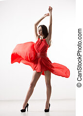 Young beauty woman in fluttering red dress White background...