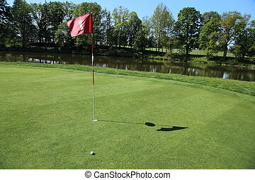 green of a beautiful golf course - golf ball next a flag on...