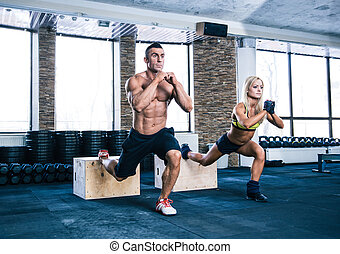 Woman and man working out at gym - Woman and man working out...