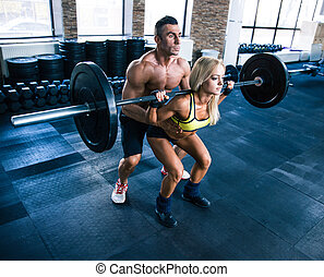 Woman workout with barbell and trainer at gym