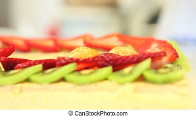 hands pastry chef prepares a fruit cake