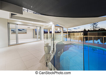 Pool and deck in modern mansion at dusk.