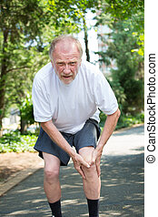 Older man grasping knee in pain - Closeup portrait, older...