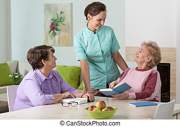 Two elderly women and a friendly nurse - Two elderly women...