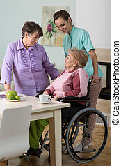 Woman on wheelchair, friend and nurse - Women sitting on a...