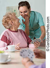 Nurse helping with cards - Nurse whispering with an elderly...