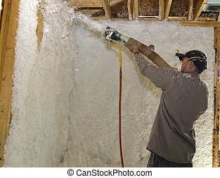 Blowing Insulation - Direct Aim - Worker blowing insulation...