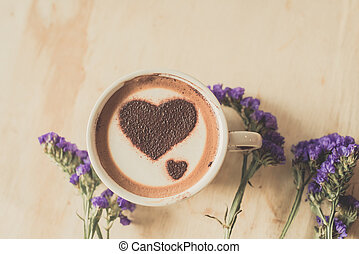 Heart shape on coffee cup on wooden background with vintage...