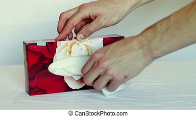 Human hand pulls tissues out of the box.