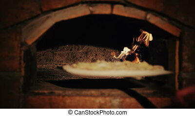 Pizza making - Cheef puts pizza into the wood burning oven...