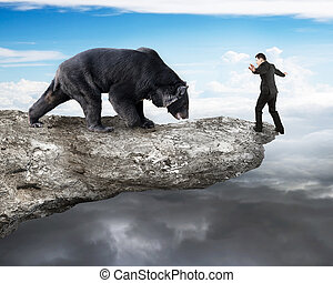 Businessman against black bear balancing on cliff with sky cloud