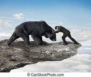 Businessman fighting against black bear on cliff with sky clouds
