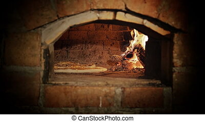 Opening in the wood stove - Pizza baking in a wood burning...