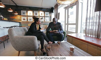 Young people at cafe doing business - Young african people...
