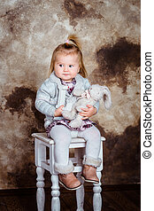 Displeased blond little girl sitting on white chair and...