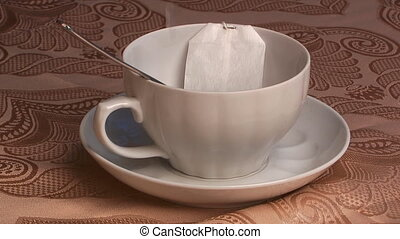 Tea in bag - The boiled water stream flows in a cup with tea...