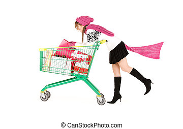 shopper - happy teenage girl with shopping cart over white