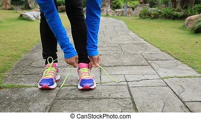 woman tying shoelace - young asian woman tying shoelace on...