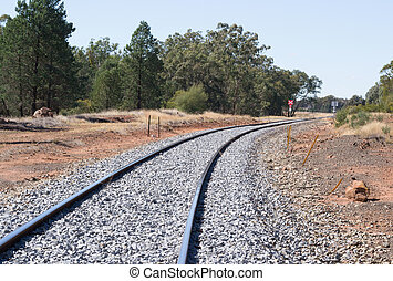 transport - a railway line curves around a bend with a...