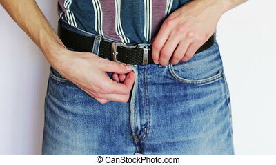 The man fastens his pants to jeans. - Man buttons lock the...
