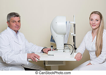 Young woman having her eyes examined by an eye handsome...