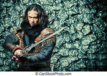 reenactment - Ancient male warrior in armor holding sword....