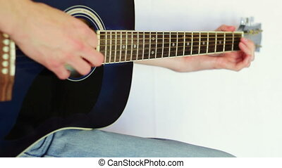 Man playing acoustic guitar - A man dressed in jeans and a...