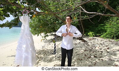 handsome groom in black trousers buttons white shirt up...
