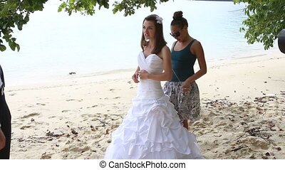 assistant helps bride tie corset of wedding dress on beach -...
